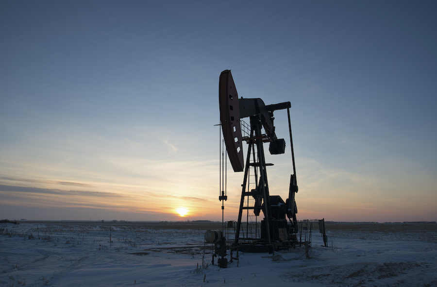 An oil drilling rig and pumpjack on a flat plain in the Canadian oil fields at sunset.