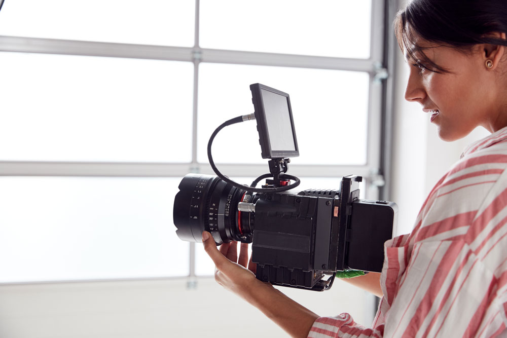 female-videographer-with-video-camera-filming-movi-ZP2JN4G