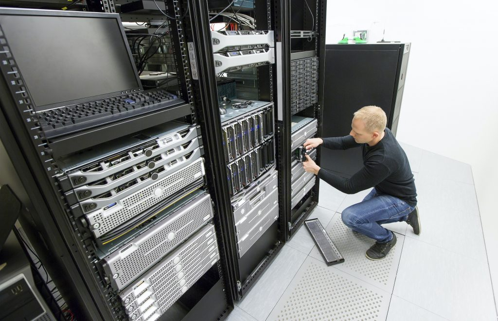 It engineer or technician maintaning storage area network SAN in data rack. Shot in datacenter.