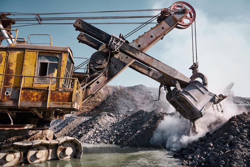 Huge quarry bucket excavator works in a hot outdoors slag dump. Heavy industrial metallurgical foggy landscape