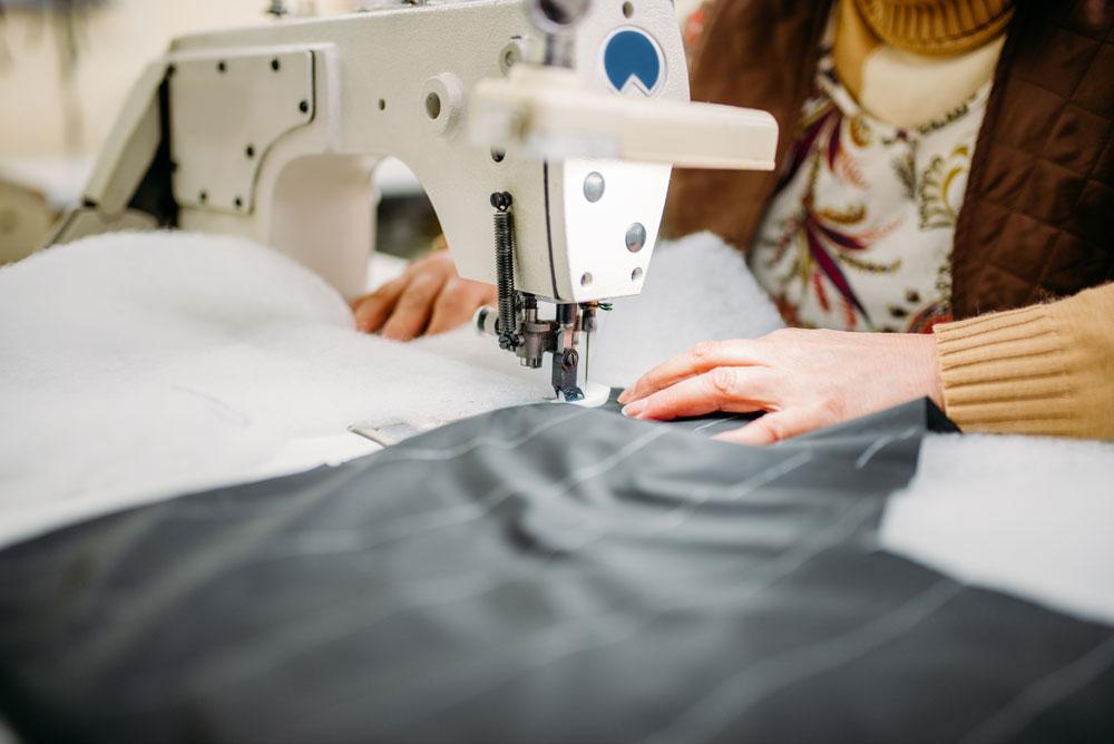 seamstress-sews-fabrics-on-a-sewing-machine-P75HEBQ