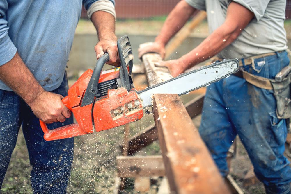 workers-handymen-cutting-timber-wood-using-mechani-P6CUBWX