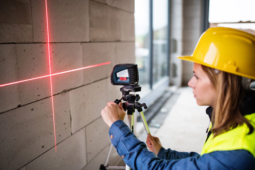 young-woman-worker-with-laser-on-the-building-site-PJFJZH6